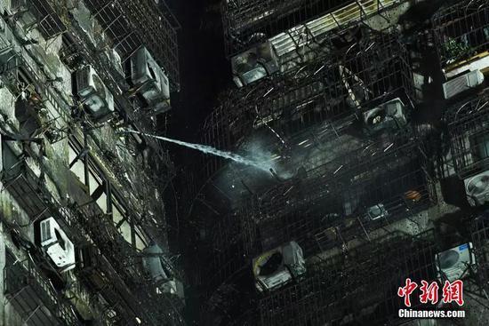 图为消防员在重庆火灾现场冲水。陈超 摄
