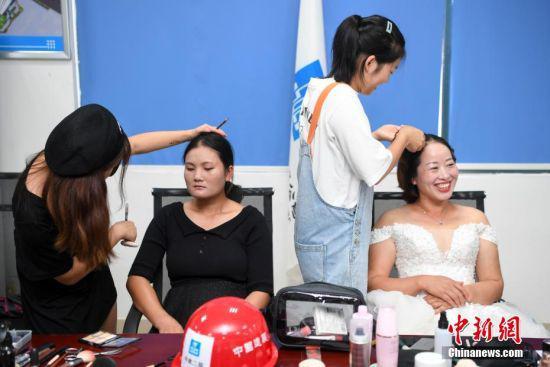 化妆师为女工人们化妆。 杨华峰 摄