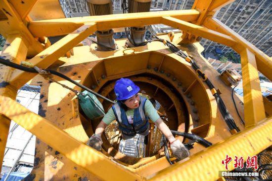 结束拍摄的塔吊驾驶员刘萍爬上塔吊作业。 杨华峰 摄