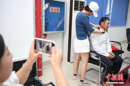 刘萍拍摄丈夫唐金龙化妆,唐金龙是一位塔吊指挥员。 杨华峰 摄