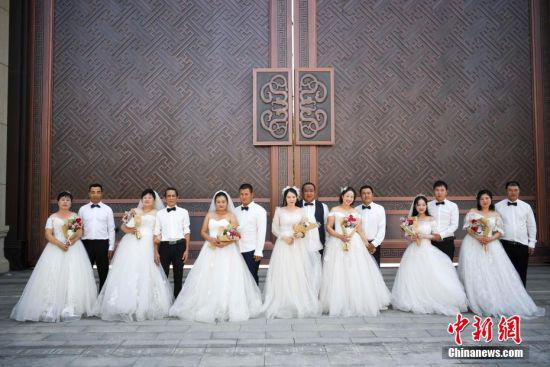 8月24日,长沙岳麓区的一建筑工地上,中建二局为该工地上的7对工人夫妻免费拍婚纱照。工人们身着婚纱与西服在园林与工地外取景拍摄,迎接七夕节的到来。杨华峰 摄