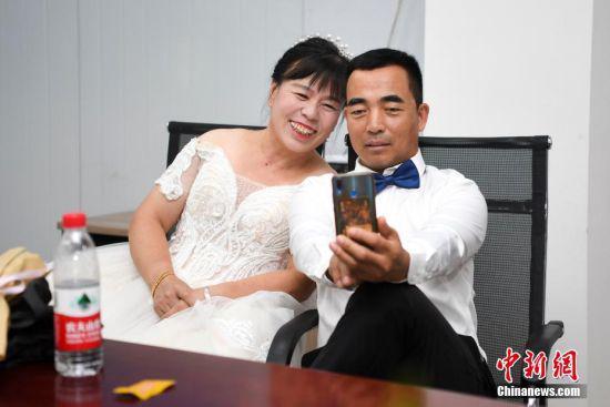 化完妆的水电仓管员刘怀斌与妻子王丽芳合影。 杨华峰 摄