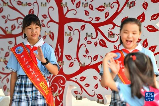 9月2日,在长沙市天心区仰天湖桂花坪小学,入校的学生互相打招呼问好。新华社记者 陈泽国 摄