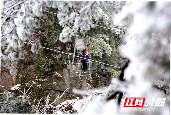 黄石寨索道检修工在冰雪天气中对索道进行巡检。