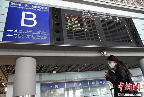 资料图:4月8日,北京首都机场3号航站楼,一名女子经过到达航班信息屏。中新社记者 侯宇 摄