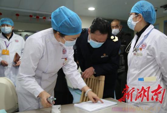 1月23日,省卫生计生综合监督局局长、党委书记张辉(左一)在湖南省脑科医院门诊大厅查看发热患者预检分诊登记表。黄栋 摄