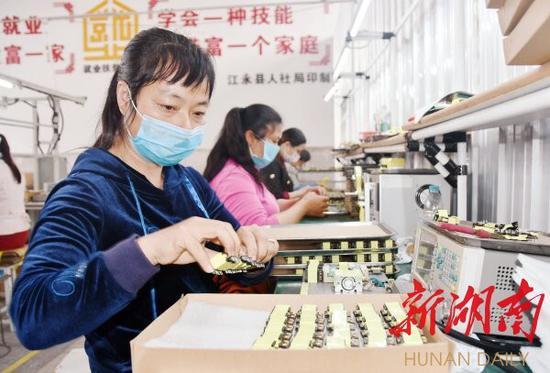 """3月1日,江永县桃川镇锦堂村某电子加工""""扶贫车间"""",工人在生产微型变压器。目前,全县32个村的就业""""扶贫车间""""全部复产。 田如瑞 摄"""