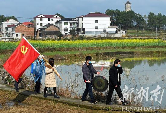 (2月9日,洞口县高沙镇云峰村,党员志愿者在走村穿巷敲锣提醒村民加强疫情防控。滕治中 摄)