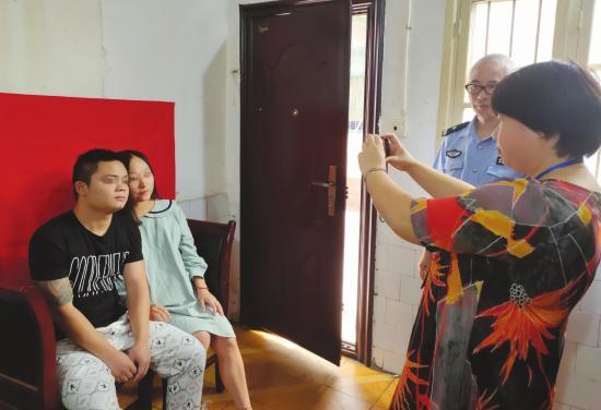 ▲近日,益阳安化看守所,王勇(左)和邓丽在临时拉起的红布前拍结婚证件照。图/受访者提供