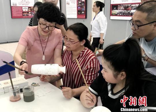 参观者学习如何在瓷瓶上填色。 邓霞 摄