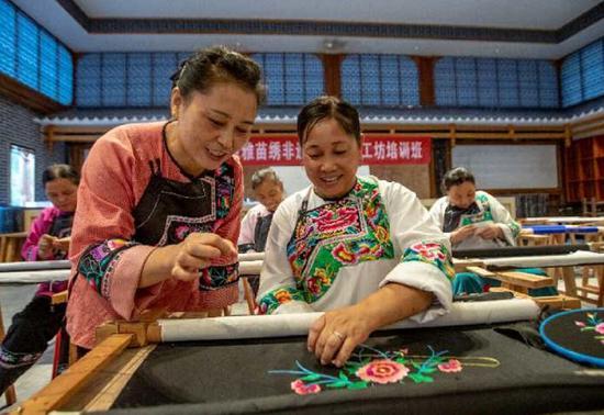 左一绣娘石美梅正在教村里的妇女绣苗绣。石林荣摄