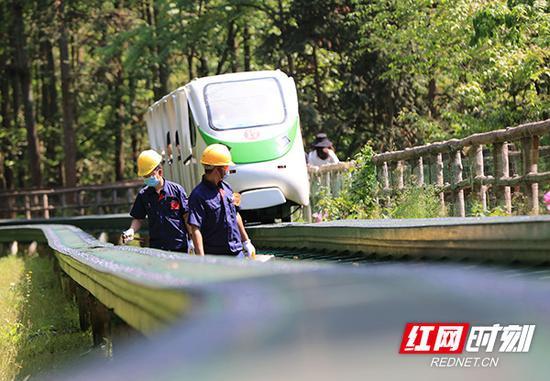 5月1日,湖南张家界武陵源景区十里画廊观光电车巡检员在检查电车运行情况,并要求戴口罩。吴勇兵 摄