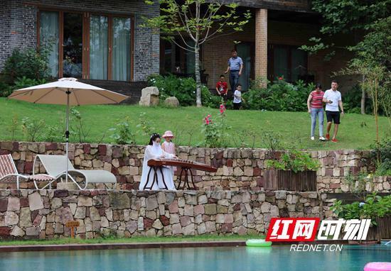 8月14日,一名女人在梓山漫居为游客演奏。暑期,武陵源乡村民宿成热门。(吴勇兵 摄)