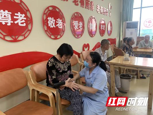 老人陈俭紧紧攥着护理主任崔清梅手,向她表示感谢。