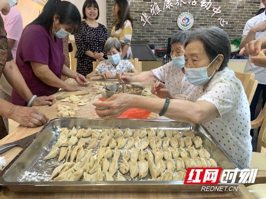 沿桌而坐的几位耄耋老人正在护理人员的陪伴下,乐呵呵地包饺子。