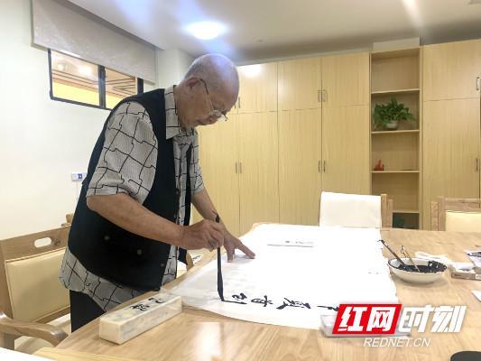 老书法家谢文华正在挥毫泼墨,勤练书法。