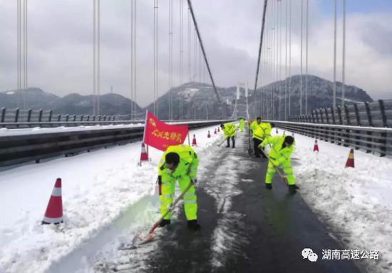 △近日,湘西吉首矮寨大桥,工作人员正在桥面上铲除积雪。