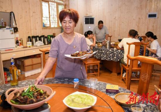 (8月12日,沅陵县官庄镇界亭驿村金州湾驿站,黄三妹在为客人上菜。)