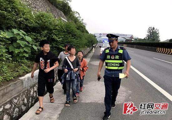 邵东路政大队队员及时制止正在高速上互相追逐的少年。