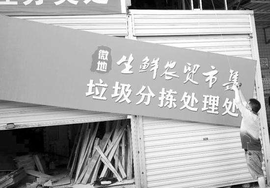 7月1日,长沙市雨花区微地生鲜农贸市集,工作人员正在悬挂垃圾分拣处理处的牌子。 图/受访者提供