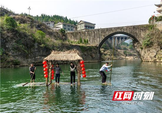 青山环抱、绿水奔流中,游客体验竹排竞渡。
