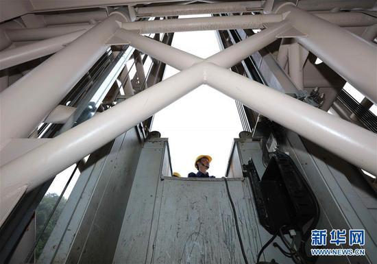 7月13日,湖南张家界市武陵源区百龙天梯工作人员在悬崖钢井架上巡检。 针对今年夏季降雨量大、持续时间长的情况,张家界市武陵源区组织各景区旅游企业在完善应急保障机制的基础上,加大对载人旅游设施的检查力度,确保汛期游览安全。 新华社发(吴勇兵 摄)