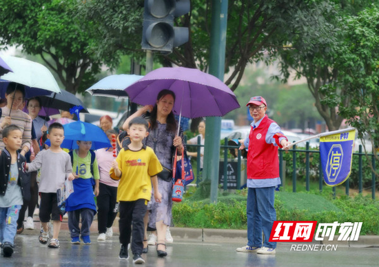 在湘龙街道湘龙路与龙塘路交会的十字路口,71岁的姚绍禹紧盯着红绿灯和路上来往的车辆,护送学生们安全过马路。
