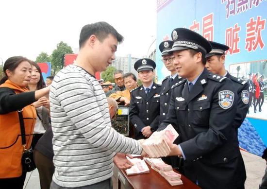图为民警将赃款返还给受害群众。