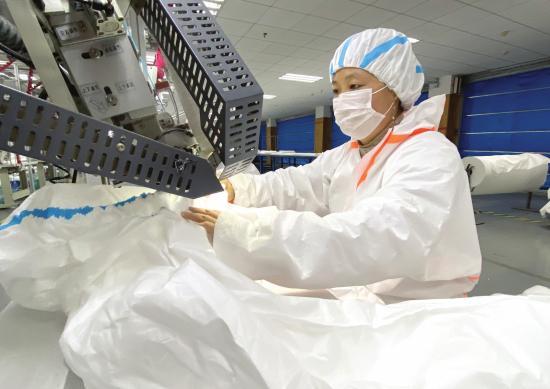 近日,梦洁家纺,工人正忙着生产防护服。图/潇湘晨报记者 陈张书