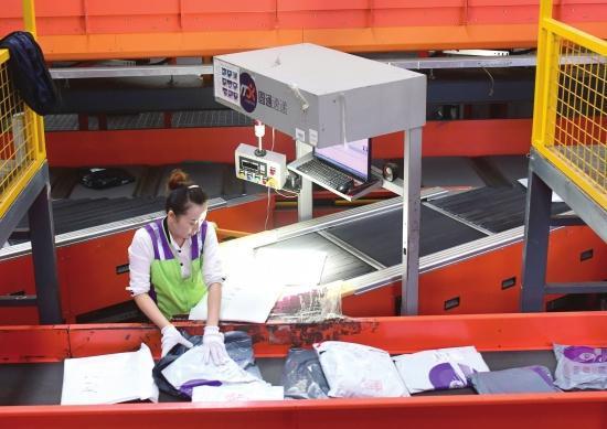 9 月 21 日,长沙临空经济示范区,圆通速递的工人正在处理包裹。 图 / 记者杨旭