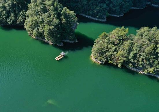 10月1日,在张家界武陵源宝峰湖景区,工作人员驾驶清漂船清理湖面漂浮物(无人机照片)。吴勇兵 摄