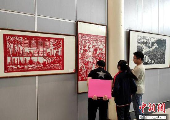 参观者驻足欣赏剪纸作品。 邓霞 摄