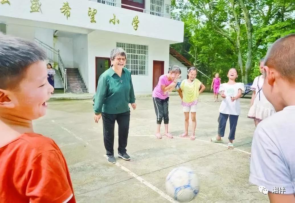 在桐林弘盛希望小学,周秀芳和学生在一起开心地玩游戏。