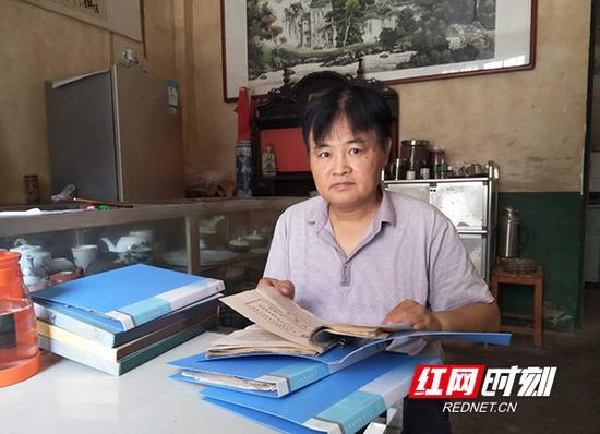 家住衡山县城的赵爱日翻阅自己收藏的物品。