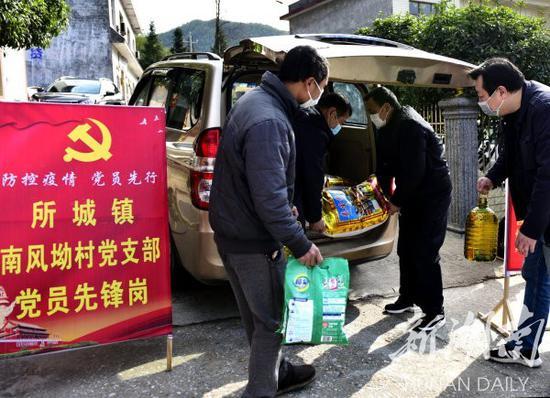 (2月10日,蓝山县所城镇南风坳村,扶贫工作队员和党员干部在搬运代购物资。 杨雄春 刘曦 摄)