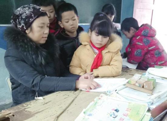 ▲湘西凤凰县三拱桥学区欧阳小学,在教室里辅导学生的龙月琼(左一)。图 / 受访者提供