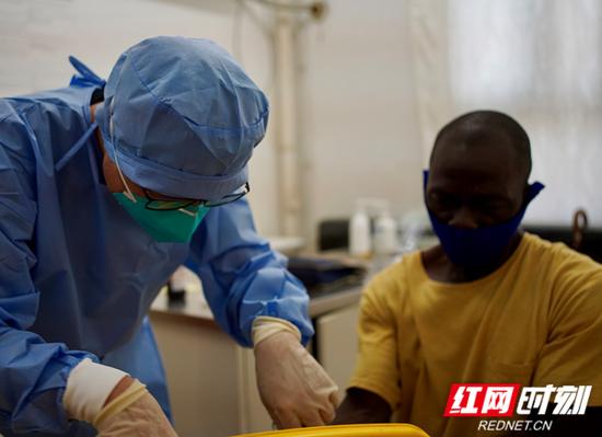 援塞医疗队队员沈民仁为患者处理伤口。