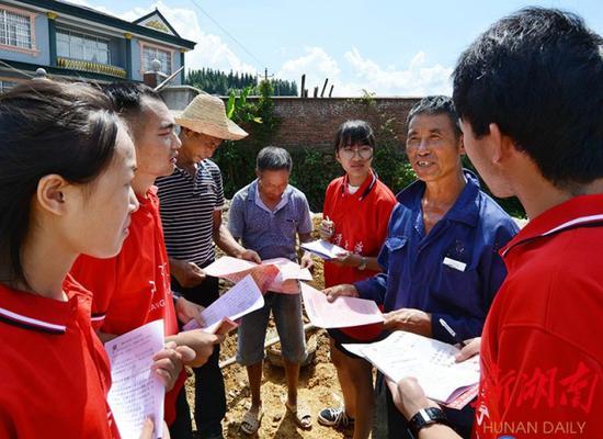 ↑2018年7月16日,洪江市雪峰镇两溪口村一建筑工地,大学生志愿者在为农民宣讲维权知识,帮助他们增强依法维权意识。(资料图片)杨锡建 摄