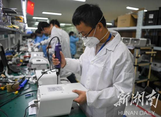 (2月10日,湖南明康中锦医疗科技发展有限公司,工作人员在检测高流量无创呼吸湿化治疗仪。湖南日报·新湖南客户端记者 傅聪 摄)