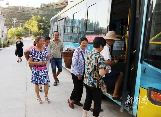 8月4日,保靖县清水坪镇贫困村黄连村,村民有序登上公交车。