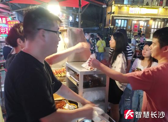 图为顾客在购买东瓜山烤肉肠(剑裘 摄)