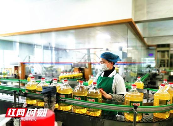 在金健植物油有限公司德山油厂的灌装车间内,戴着口罩的工人们正在生产线上忙碌着。曾玲 摄