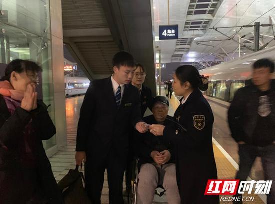 站台客运人员和该次列车长办理交接,为两位老人安排了距车门较近的座位。