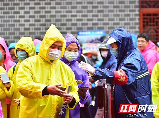 武陵源景区入口外,引导员正在依次引导游客佩戴口罩,出示居民健康码、身份证后再进入游客服务中心。姚冶 摄
