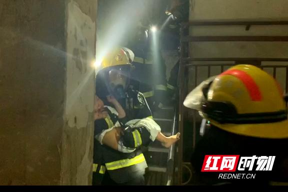 消防人员将被困的小孩抱出。