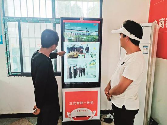 杨木村村民在服务大厅看新闻信息。