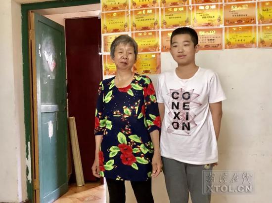 刘立华和胡洋睿在租住的家中,墙上胡洋睿的奖状让刘立华特别欣慰。