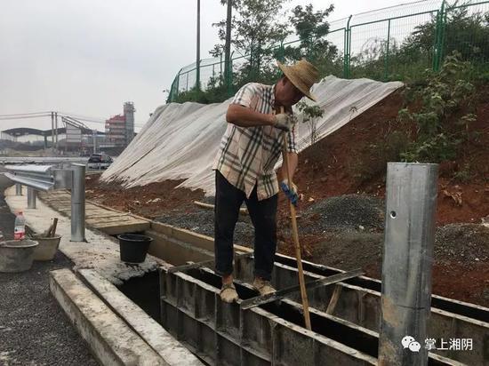 △施工人员蒋金良正抢抓时间修筑排水沟