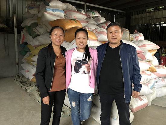 龚玉姣一家人,他们背后是今年新收的粮食。澎湃新闻记者 陈凯姿 图