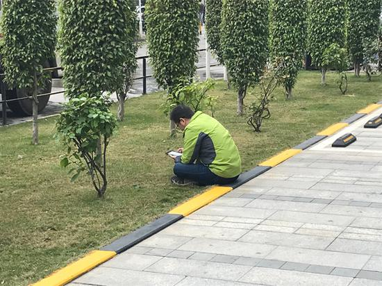 午休时间,一家公司楼下有员工正在阅读。 澎湃新闻记者 沈文迪 图